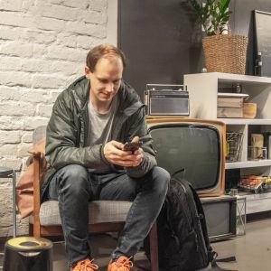 Peter Sunde Kolmisoppi petar på sin mobiltelefon i en fåtölj i Parads väntrum bredvid en gammal tv.