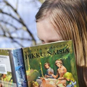Tyttö lukee kirjaa Pikku naisia