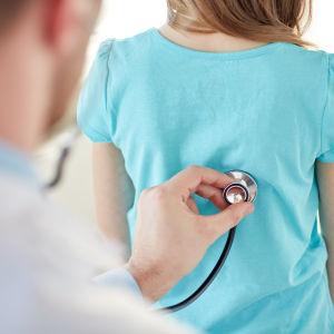 Läkare undersöker ett barn med stetoskop.