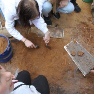 Barn på arkeologiska utgrävningar som håller upp krukskärvor som det hittat.