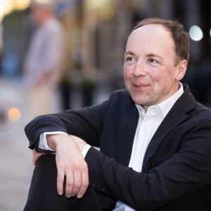 Jussi Halla-aho istuu ja hymyilee Iso-Roobertinkadulla.