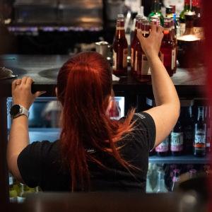 Tarjoilija täyttää kylmäkaappia juomilla ravintolassa.