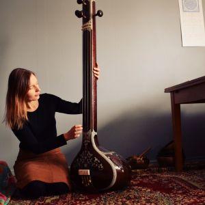 Laura Naukkarinen sitter på knä och spelar på ett indiskt stränginstrument i ett rum med turkisk matta och blå vägg.