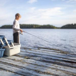 En pojke står och fiskar på en brygga.