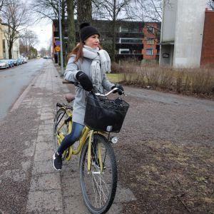 Mimosa Koskimies on pyöränsä päällä Hämeenlinnan keskustassa.