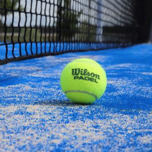 En grön padelboll bredvid ett nät på en blå spelplan.