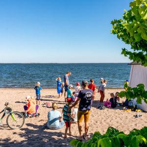 Ihmisiä tuulisella uimarannalla.