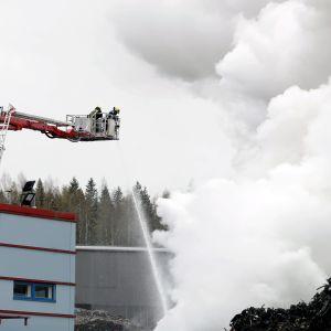 Vattenstråle riktas från en lyftkran ner mot ett moln av brandrök. Brandmän arbetar under en eldsvåda i Tammerfors den 11 maj 2020.