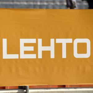 Lehtos logga på en orange banderoll.
