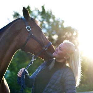 Personporträtt på Emilia Hellman brevid sin häst