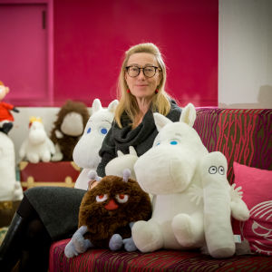 Sophia Jansson bland en massa muminfigurer på en röd soffa.