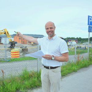 Man i vit kragskjorta framför byggarbetsplats på stor grusplan med stängsel omkring. Mannen pekar mot arbetsplatsen.