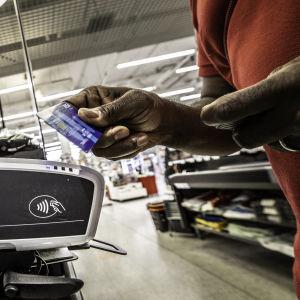 En hand håller i ett blått visakort och för det mot en betalningsautomat vid en kassa.