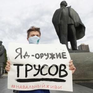 En man i munskydd står bredvid en staty och håller upp en skylt där det på ryska står gift är ett vapen för ynkryggar. Hål dig vid liv Navalnyj.