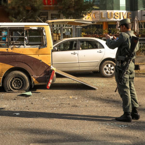 En soldat står bredvid en minibuss som har flera hål av splitter.