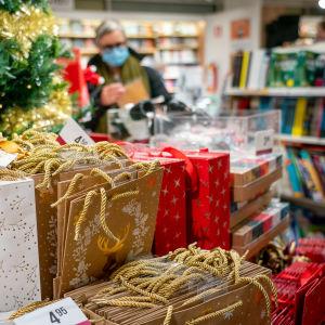 Nainen katselee joululahjoja kirjakaupassa hengityssuojain kasvoillaan.