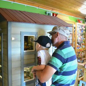 En man lyfter upp ett barn för att det bättre ska kunna titta in i ett stort dockskåp.