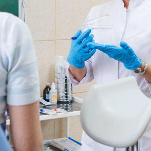 En läkare drar på sig blå plasthandskar medan en kvinna som man endast ser ryggen av sitter i en gynekologisk undersökningsstol.