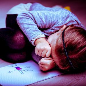 Ett olyckligt barn ihopkrupet bredvid en teckning.