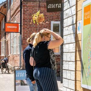 Turister står och betraktar en informationskarta vid ett gammalt hus.