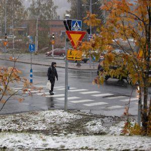 En människa klätt i mörka kläder går över en gatukorsning. Det är regnvått på gatan, men på gräsmattorna runt omkring ligger ett lätt snötäcke och det är fortfarande löv på träden omkring.