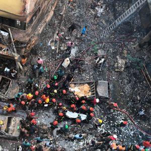 Räddningsarbetare bär ut ett offer från storbranden i Dhaka