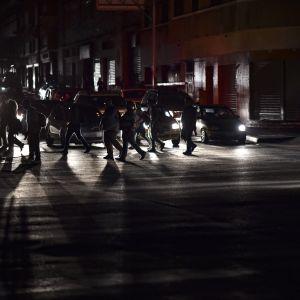 Människor korsar en gata under elavbrott i Caracas 7.3.2019