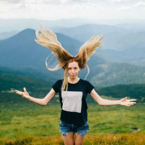 Yksinäinen nainen seisoo oudossa asennossa vuoristossa.