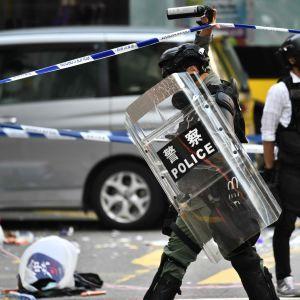 Poliser vid avspärrningarna runt den plats där en demonstrant sköts i Hongkong på måndag morgon.