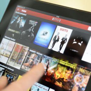 Ett finger som drar över en skärm där Netflixappen är öppnad.