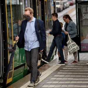 En man stiger på spårvagnen i centrala Helsingfors. Han bär ett svart munskydd.