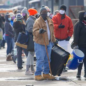 Talvivaatteisiin pukeutuneita ihmisiä jonossa erilaisten astioiden ja säiliöiden kanssa