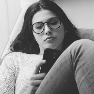ledsen flicka sitter med en mobiltelefon i handen