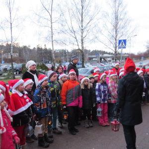Skolelever utklädda till tomtar firar julfest i Karis.