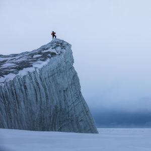 En person står uppe på en glaciärkant i Antarktis.