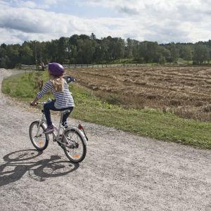 Flicka cyklar på landsväg.