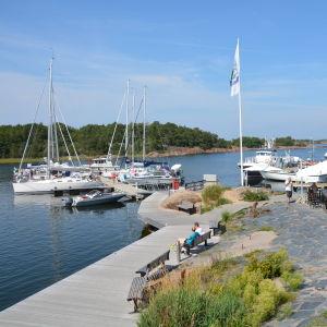 Segelbåtar i Örö gästhamn, och kafégäster i hamnen.