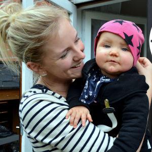 Kvinna med barn i famnen.