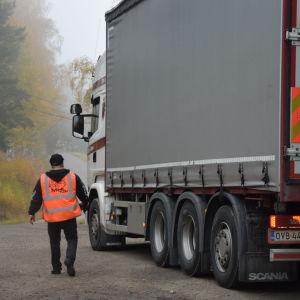 en man med keps o orangefärgad reflexväst som går mot lastbilshytten på en långtradare.