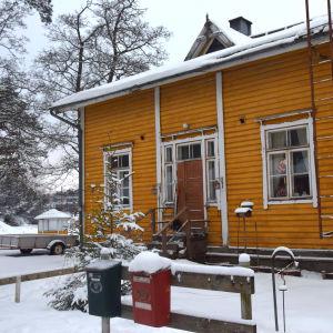 En gul trävilla, gammal arbetarbostad med fler bostäder. Målfärgen flagar, stockarna är ruttna vilket lett till hål i ytterväggarna. Den här delen är ändå i hyfsat skick, det bor en hyresgäst i denna ända av huset.