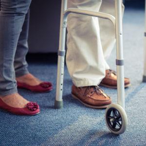 Två personers fötter och en rollator.