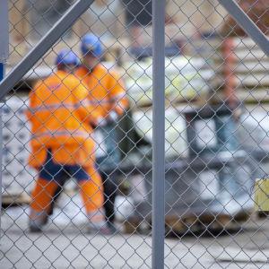 Två byggarbetare i orange overaller fotade genom ett nätstängsel