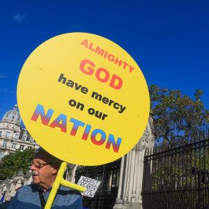 Mielensoittaja toivoo kyltissään, että Jumala olisi armollinen Britannian kansalle.