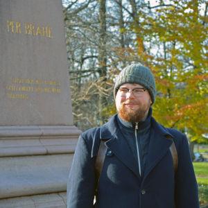 En man står bredvid Per Brahe-statyn nära domkyrkan i Åbo.