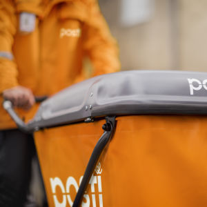 """En orange postvagn med texten """"Posti"""" på skuffas av en orangeklädd brevbärare."""