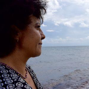 En kvinna blicar ut över en strand täckt av alger.