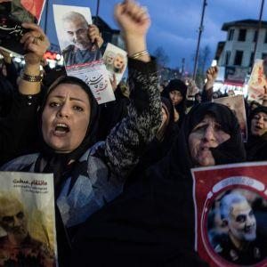 Iranilaiset naiset osoittavat mieltään pidellen käsissään Qasim Suleimanin kuvia.
