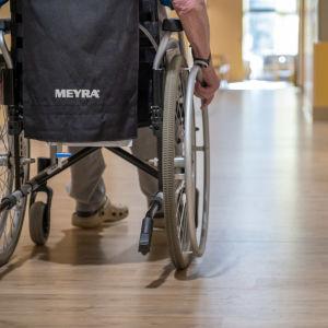 Vanhus pyörätuolissa osaston käytävällä.