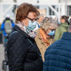 Iäkkäät ihmiset, joilla on suoja maskit Helsingin silakkamarkkinoilla.