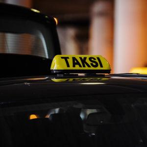 Bild på taxiskylt på biltak.